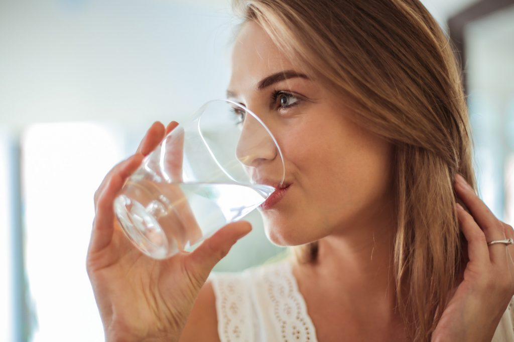 woman drinking water after wisdom teeth removal